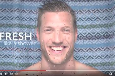 Portait eines lächelnden Mannes in Dusche mit Wassertropfen an Linse.Feigefotodesign
