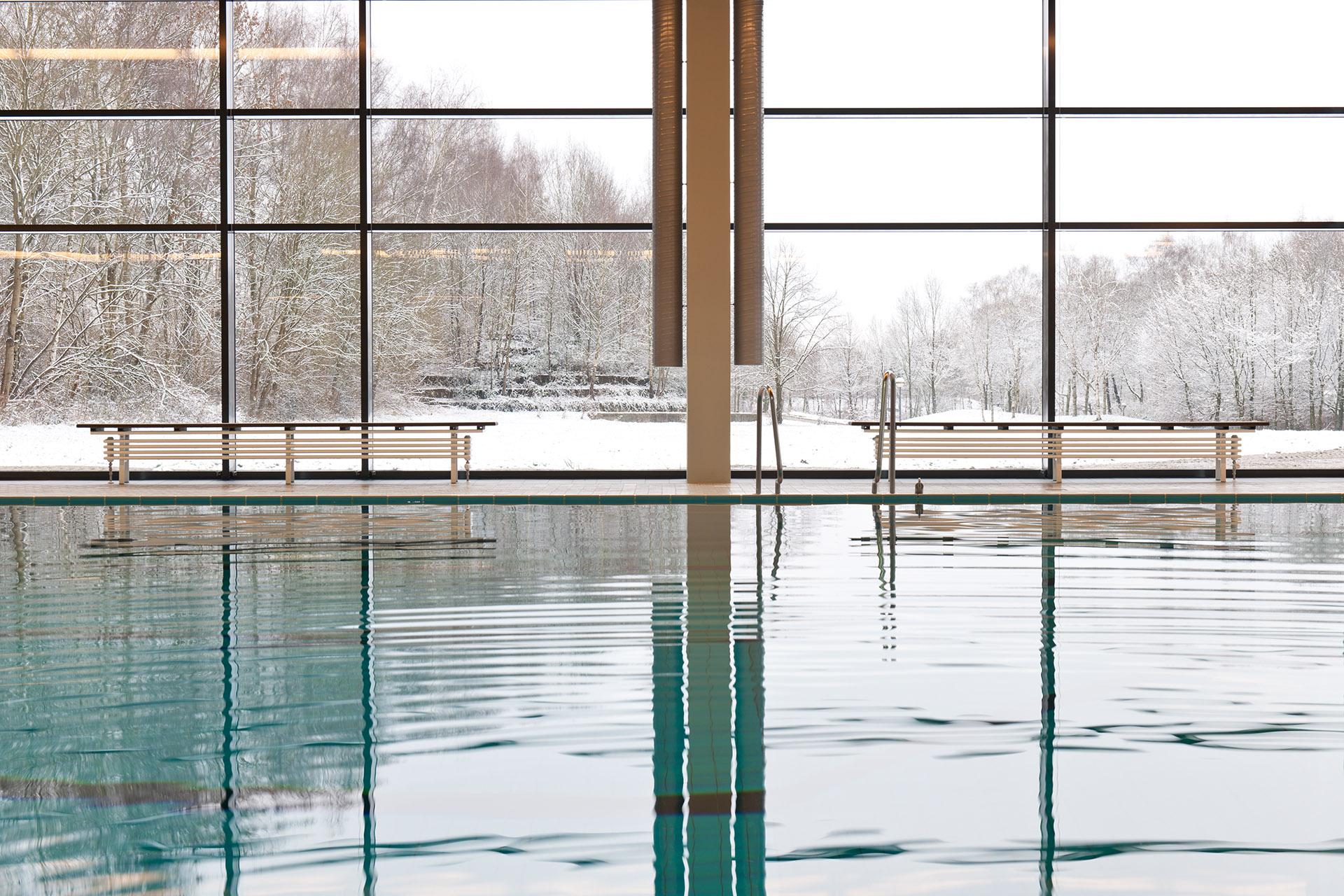 Architekturfotografie Fotograf Studio Oberfranken Ruhiges Becken im Hallenbald Selb mit Aussicht auf Rosenthalpark. Feigfotodesign