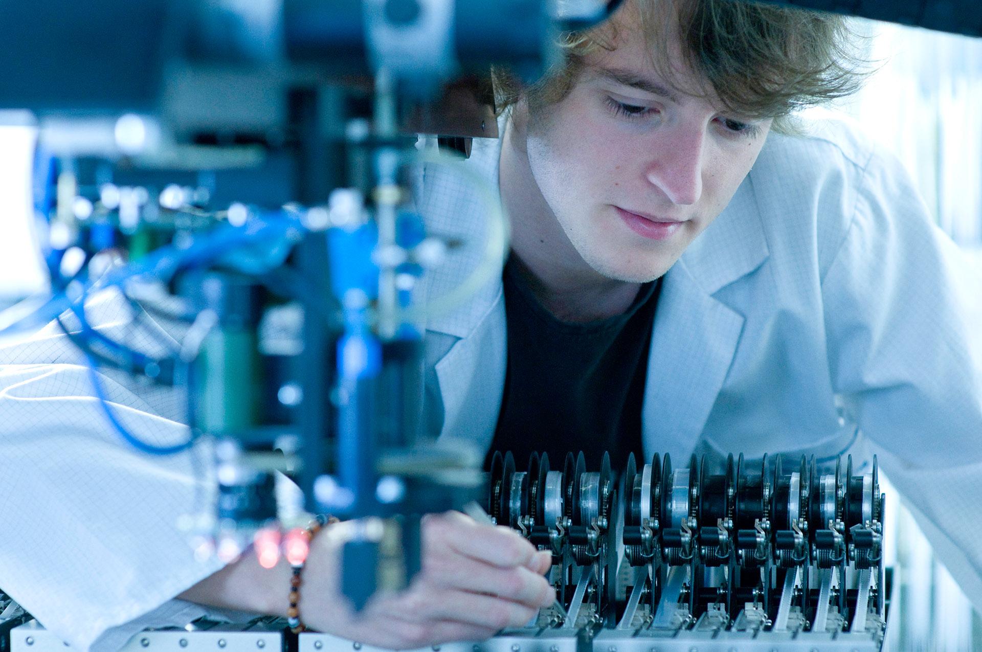 Mitarbeiter in Produktion leistet filigrane Arbeit an Maschinen. Feigfotodesign