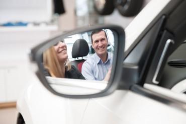 Mitarbeiter erklärt Kundin Auto, Blick über Rückspiegel