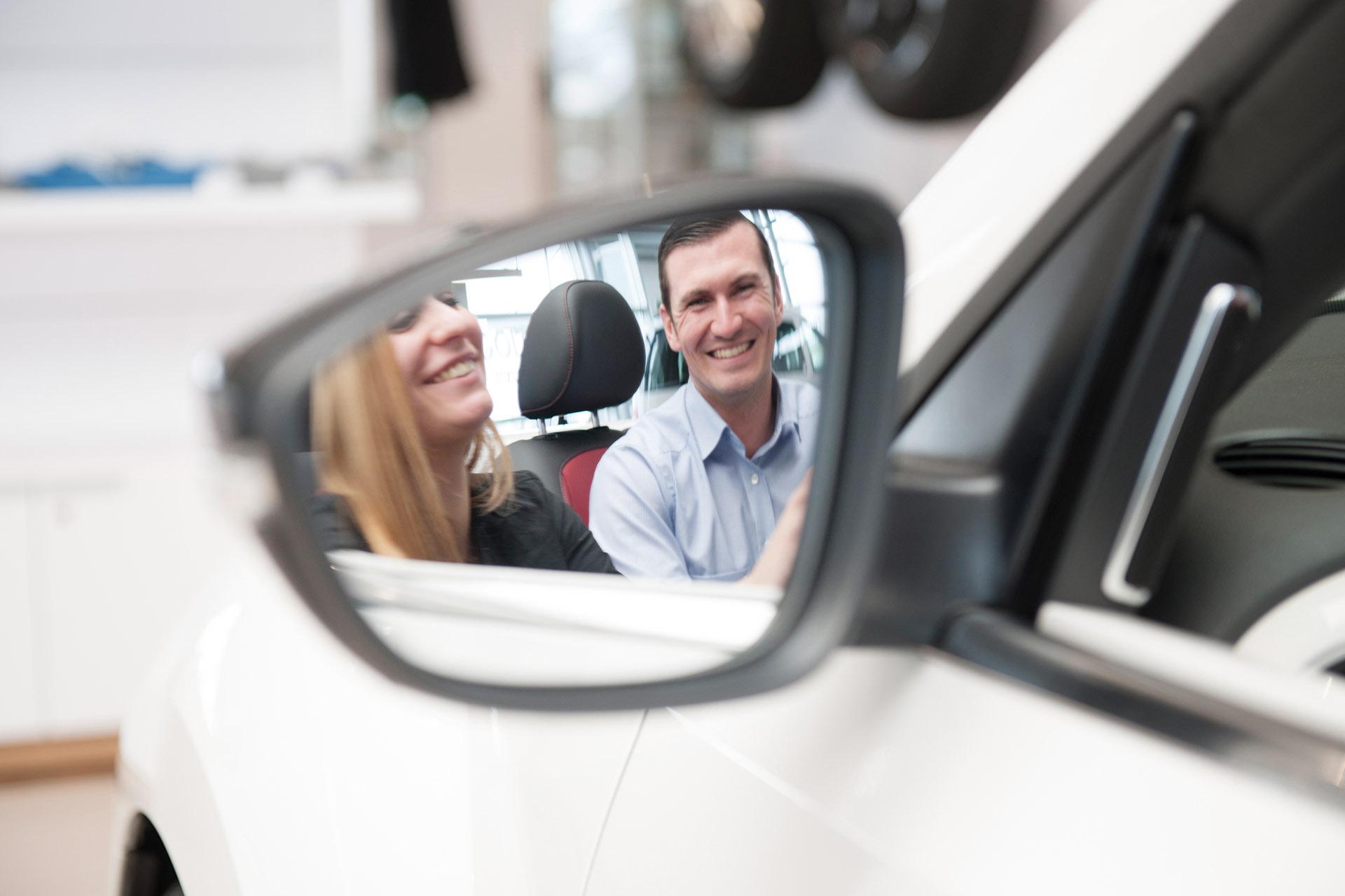 Mitarbeiter erklärt Kundin Auto, Blick über Rückspiegel. Feigfotodesign