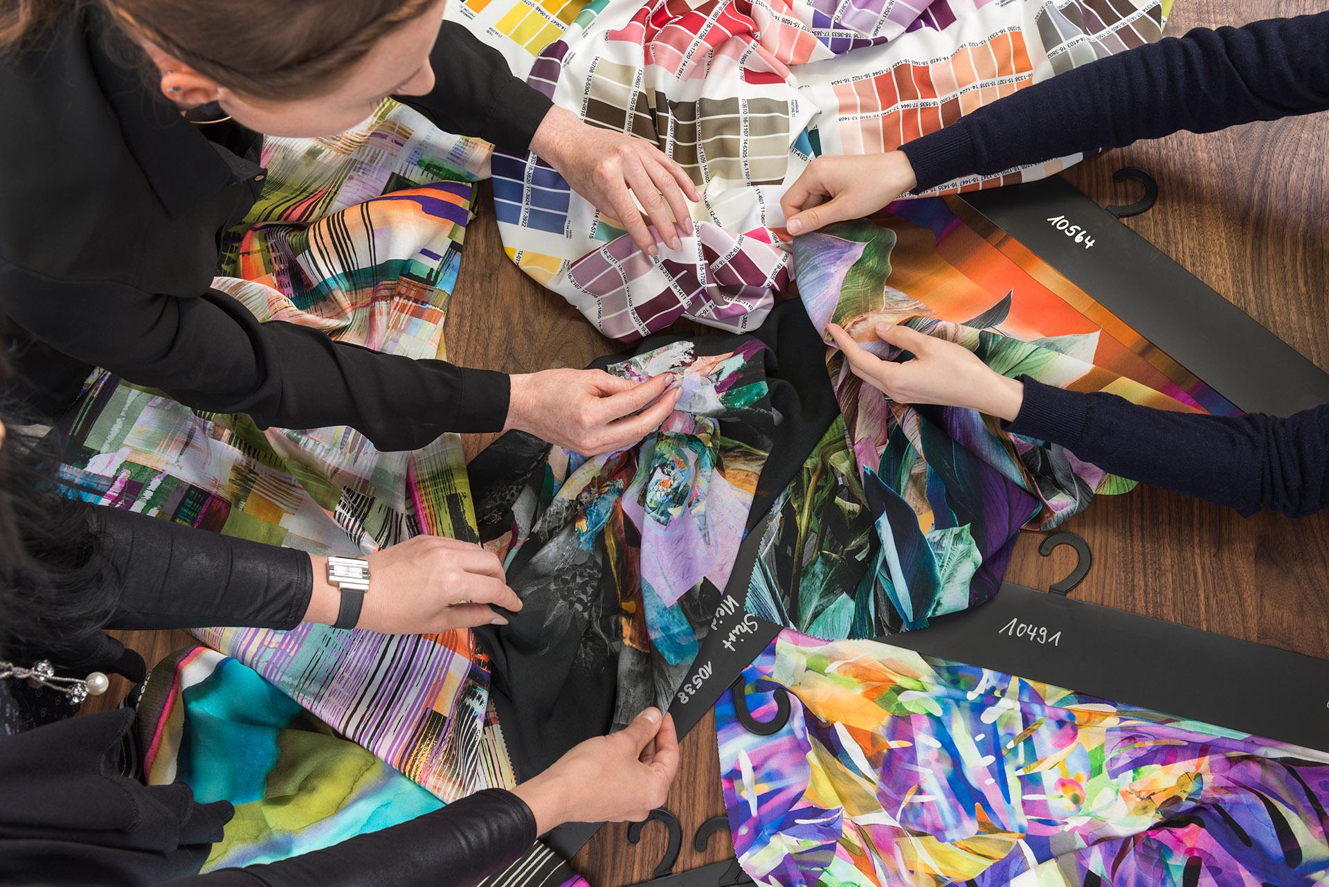 Mitarbeiterinnen bei Kollektionsbesprechung mit bunten Stoffen auf Holztisch. Feigfotodesign