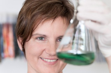 Werbefotografie Portrait von Labormitarbeiterin bei Qualitätsprüfung . Feigfotodesignmit Glas und grüner Flüssigkeit