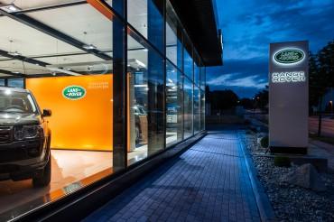 Außenaufnahme Autohaus Landrover mit Schaufenster und PKW links und Logo und Schriftzug rechts. Feigfotodesign