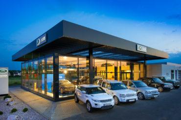 Außenaufnahme Gebäude Autohaus Landrover mit PKWs bei Dämmerung. Feigfotodesign