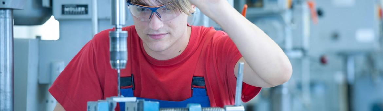 Industriefotografie Mitarbeiter mit Schutzbrille bohrt. Feigfotodesign
