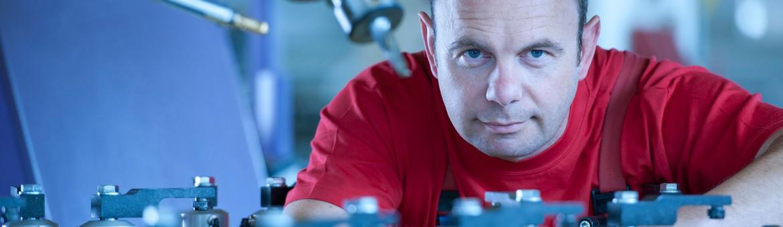 Industriefotografie Mitarbeiter an Fertigungsmaschine. Feigfotodesign