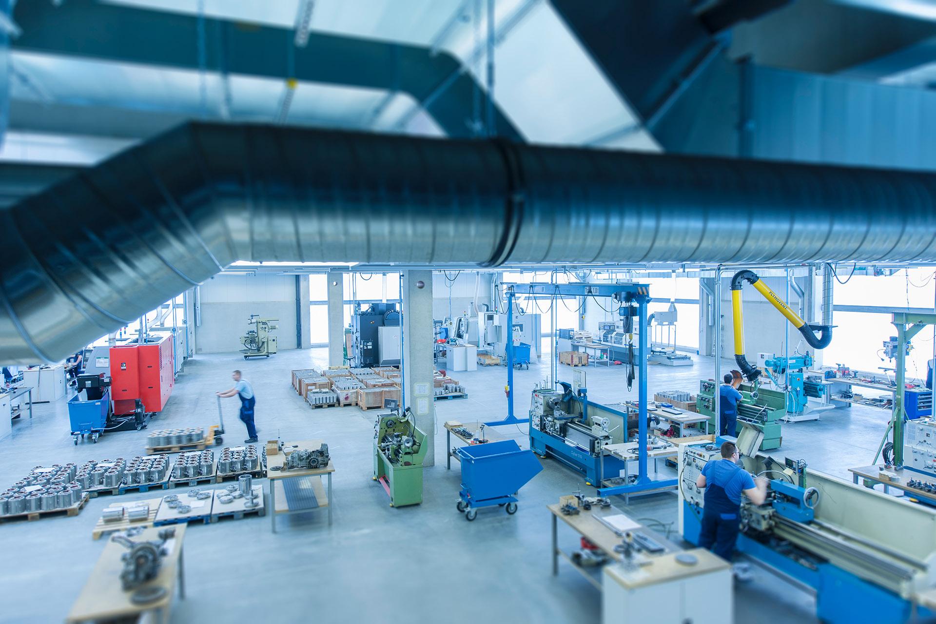 Industriefotografie Produktionshalle mit Mitarbeitern und Maschinen und Leitungen und Rohre am oberen Bildrand. Feigfotodesign