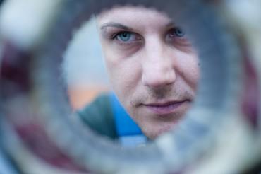 Mitarbeiter Detail Kontrolle eines Elektromotors mit Blick durch runde Öffnung. Feigfotodesign