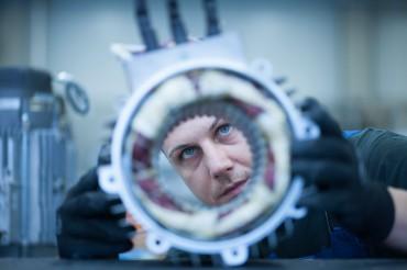 Mitarbeiter Nahaufnahme Kontrolle eines Elektromotors mit Blick durch runde Öffnung. Feigfotodesign