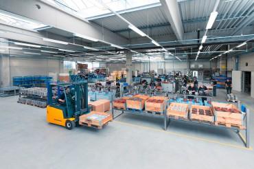 Stapler in Produktionshalle mit Material in Kisten. Feigfotodesign