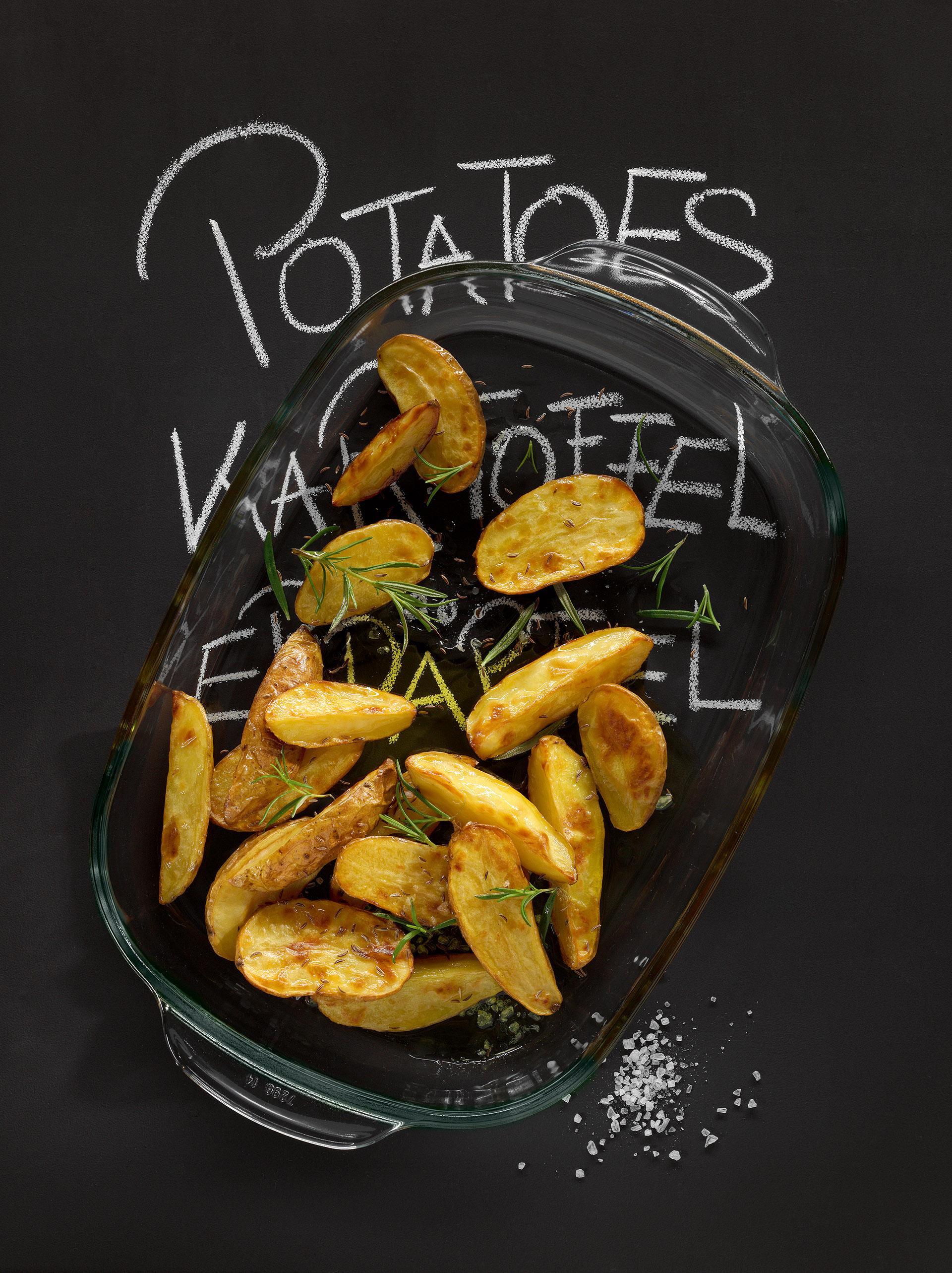 Werbefotografie Gebackene Kartoffelspalten mit Rosmarin und Salz in Auflaufform