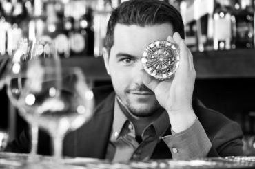 Portraitaufnahme Stephan Hinz Blick durch Cocktailglas. Feigfotodesign