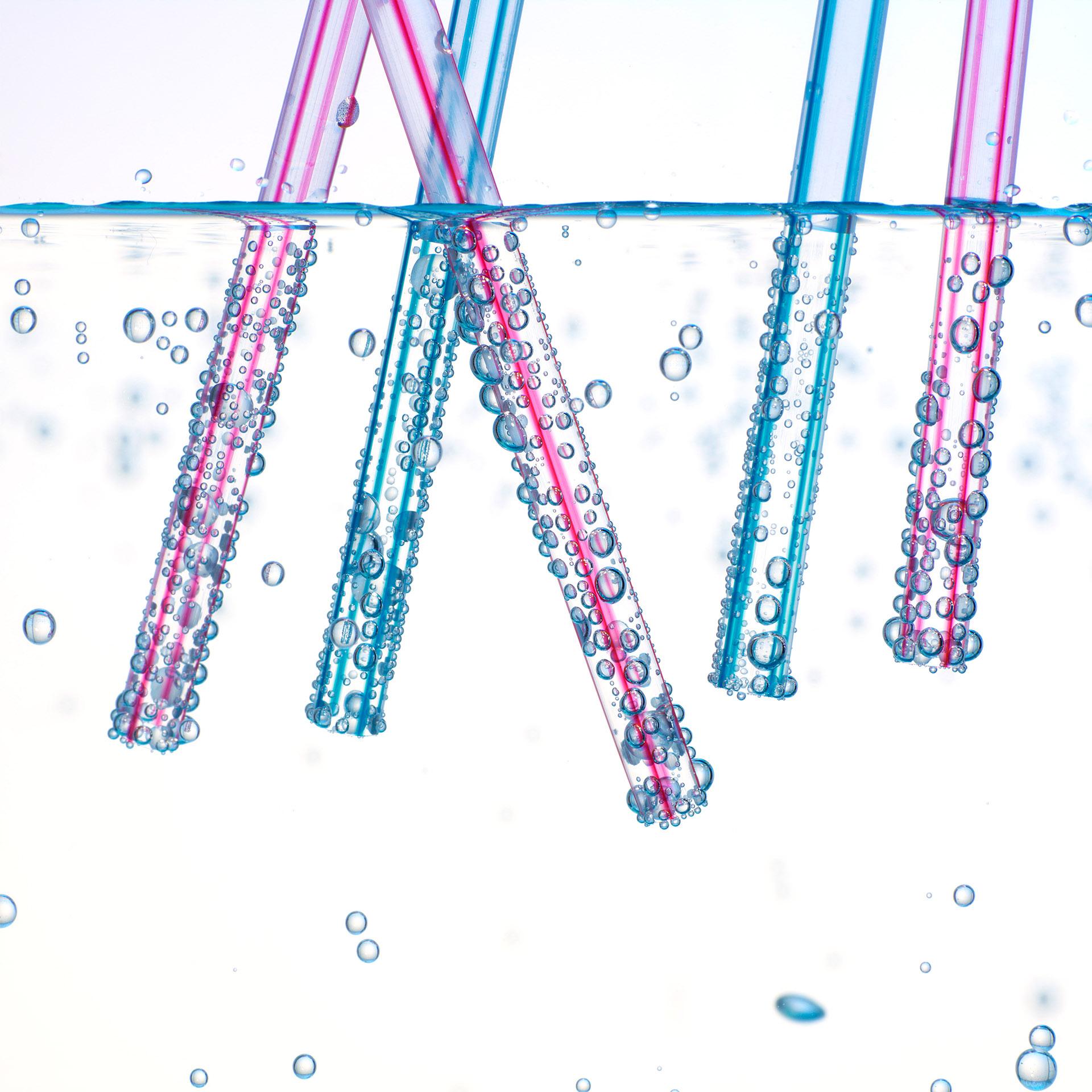 Werbefotografie Super Close-Up Strohhalme in Wasser mit Luftbläschen. Feigfotodesign