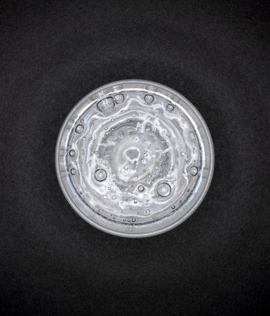 Werbefotografie Sprudeliges Wasser in Glas aauf schwarzem Hintergrund aus Vogelperspektive. Feigfotodesign