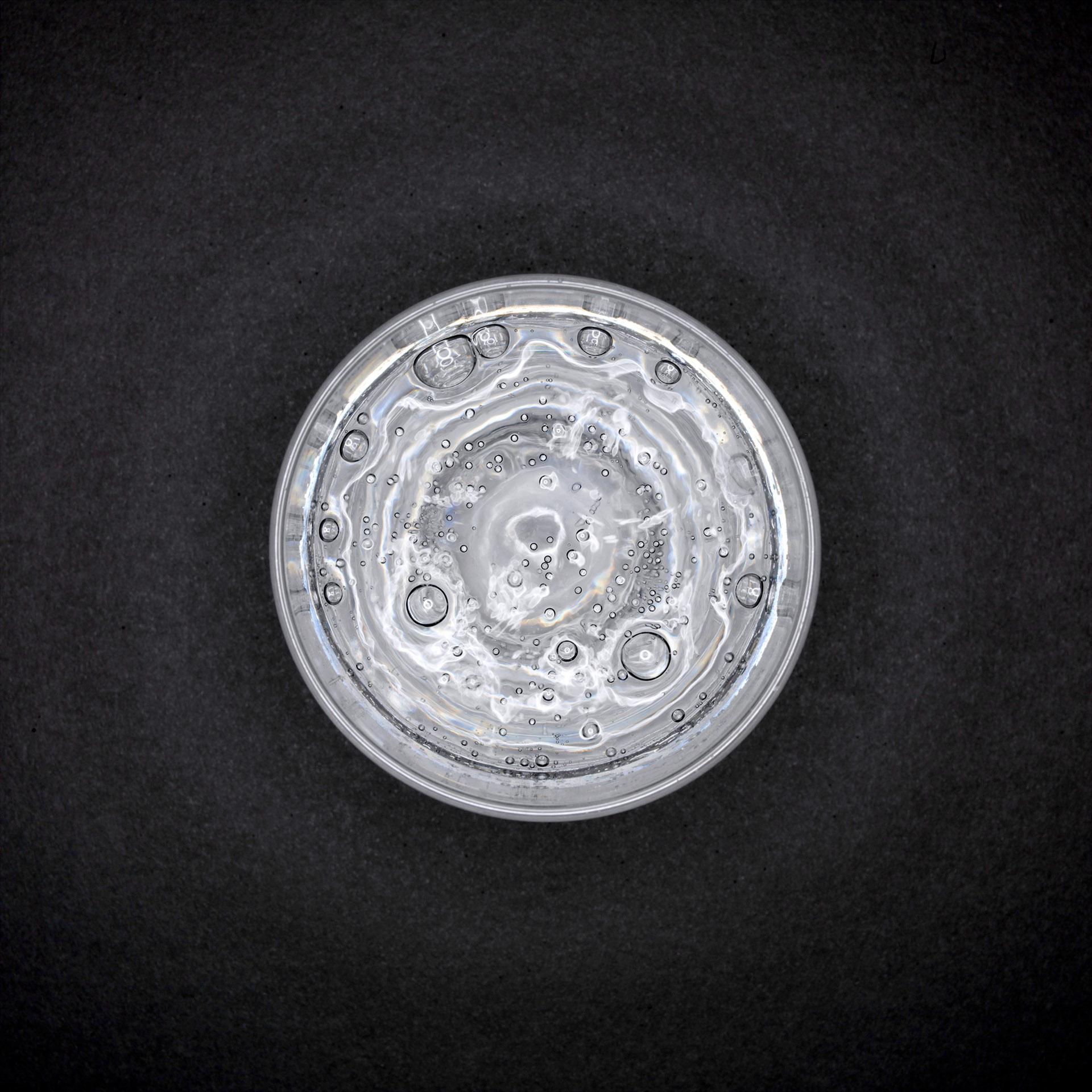 Werbefotografie Fotodesign Oberfranken Selb sprudeliges Wasser in Glas aauf schwarzem Hintergrund aus Vogelperspektive. Feigfotodesign
