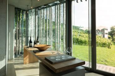 Architekturaufnahme der Vinothek von innen mit Fensterfront und Blick auf Weinberg. Feigfotodesign