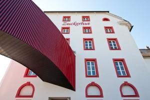 Außenaufnahme des gebäudes Zuckerhut mit weißer Fassade und roten Fenstern von Architekt Kuchenreuther