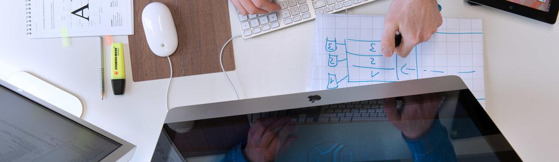 Blick auf Arbeitsplatz mit Bildschirm und Arbeitsuntensilien von oben. Feigefotodesign