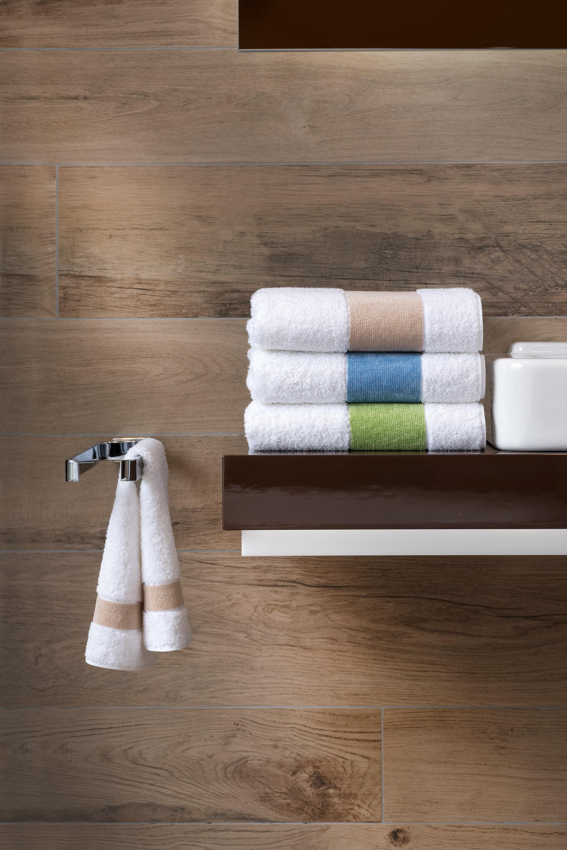 Werbefotografie bunte Handtücher der Serie Exclusiv by Feiler Frottier und Chenille gestapelt neben Waschbecken. Feigefotodesign