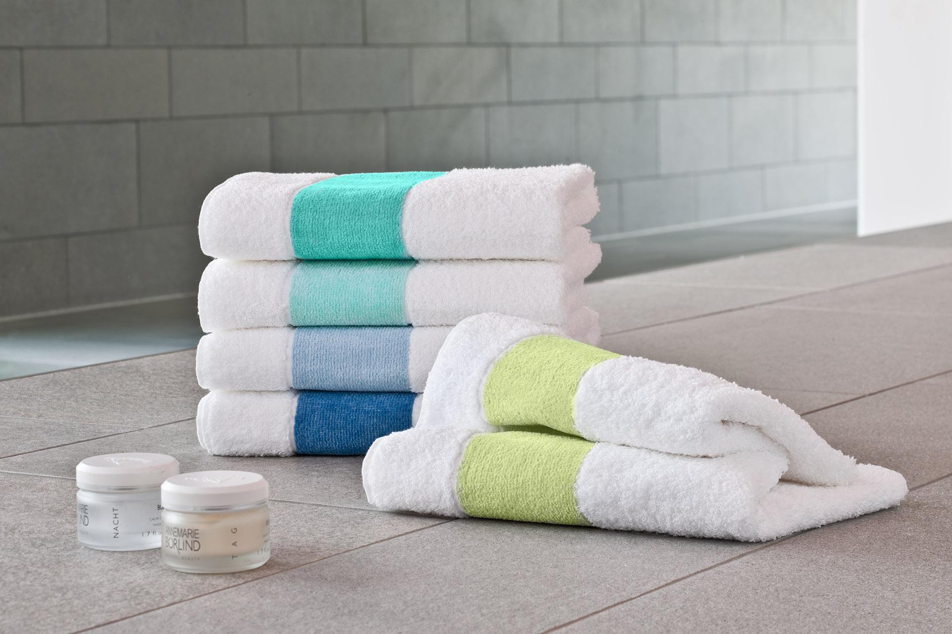 Werbefotografie bunte Handtücher der Serie Exclusiv by Feiler Frottier und Chenille gestapelt auf Badezimmerfliesen. Feigefotodesign