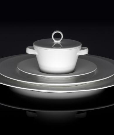 Werbefotografie weißes Porzellanservice aufeinander gestapelt auf dunkler Glasfläche. Feigefotodesign