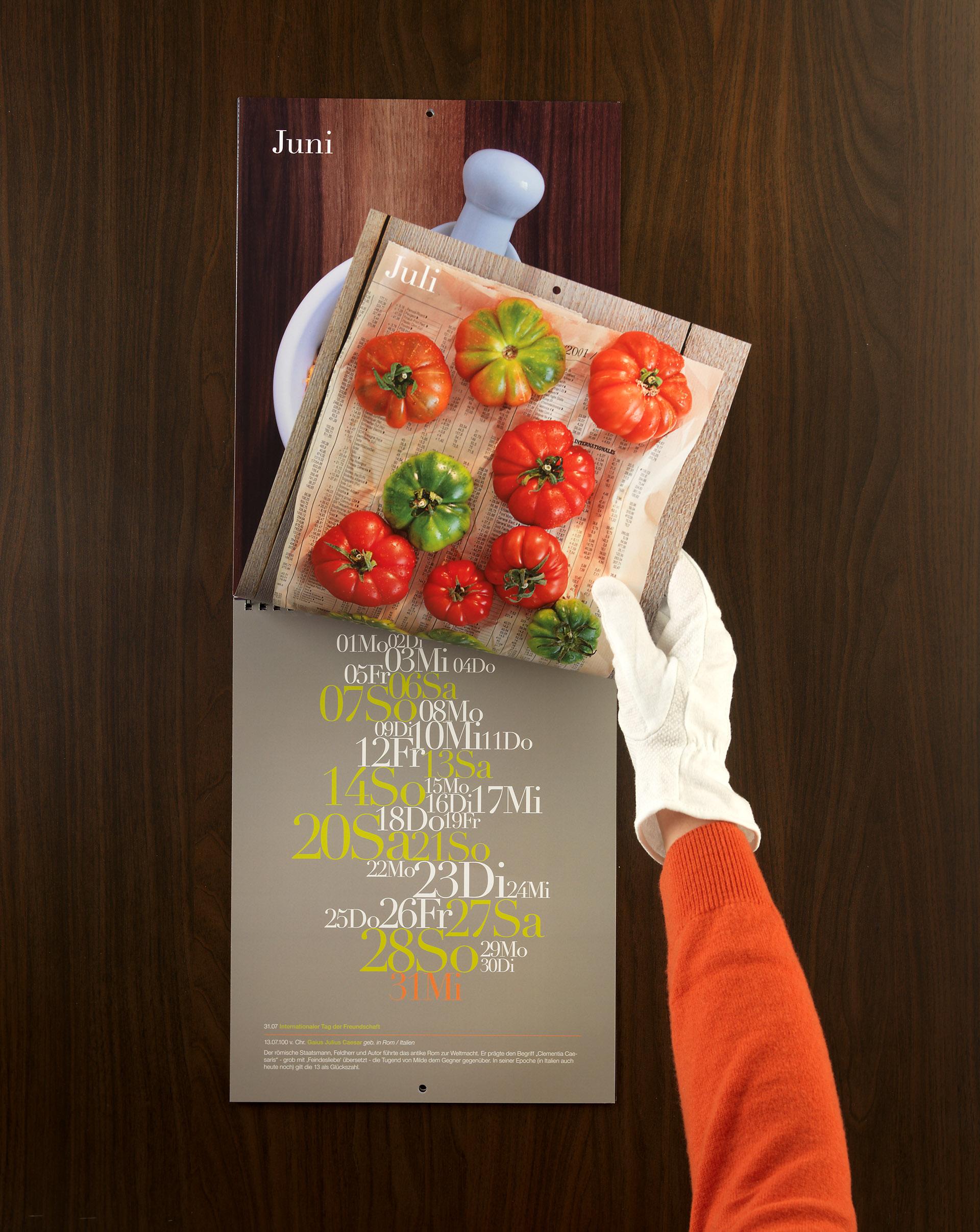 Hand mit Handschuh blättert im Kalender zu Monat Juli mit Tomaten-Motiv. Feigefotodesign