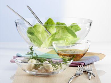 Werbefotografie Salatschüsseln in drei Größen mit Salat und Dressing Inhalt auf Holzbrett. Feigefotodesign