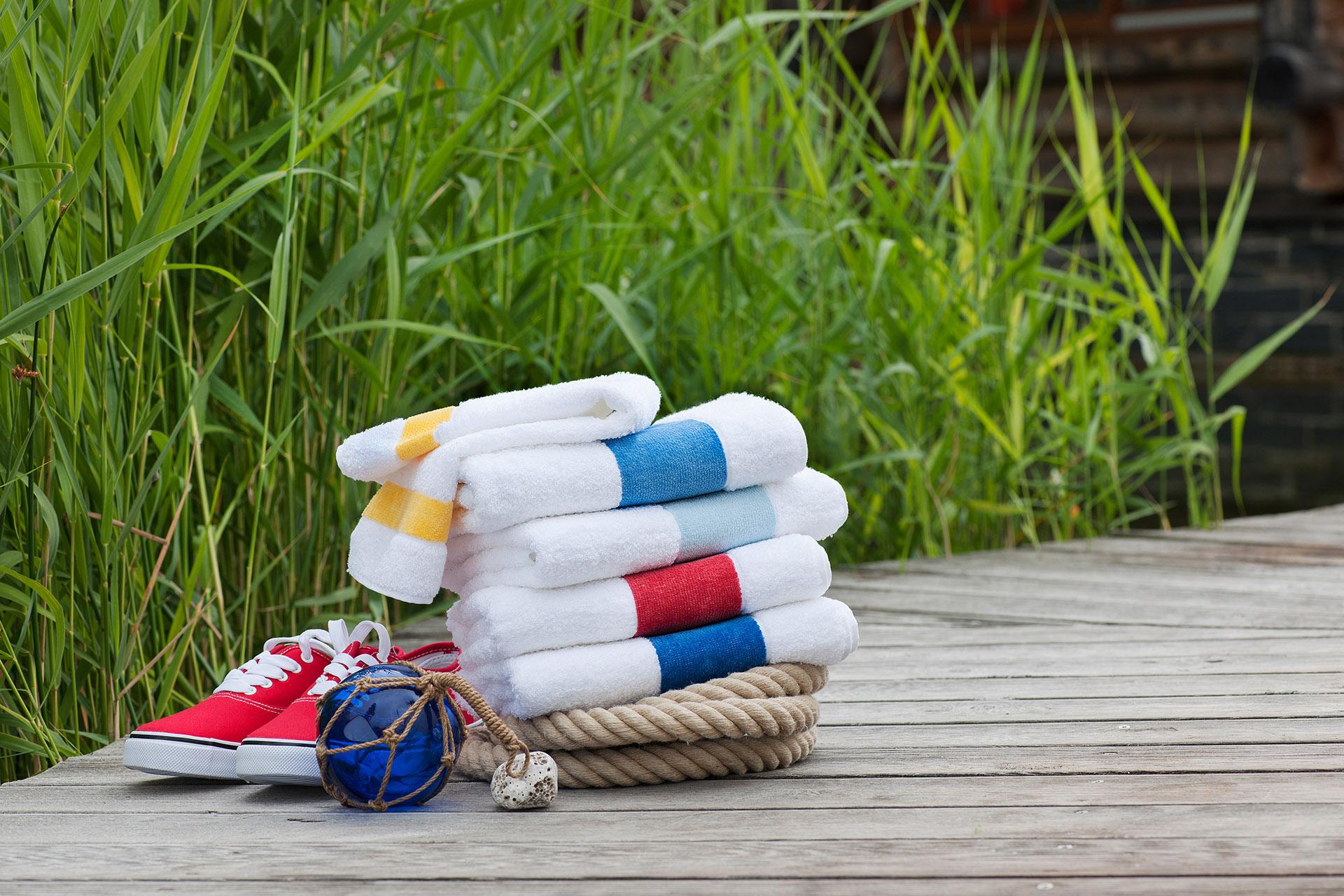 Bunte Handtücher in maritimen Farben der Serie PORTO von Feiler Chenille neben Schiffstau