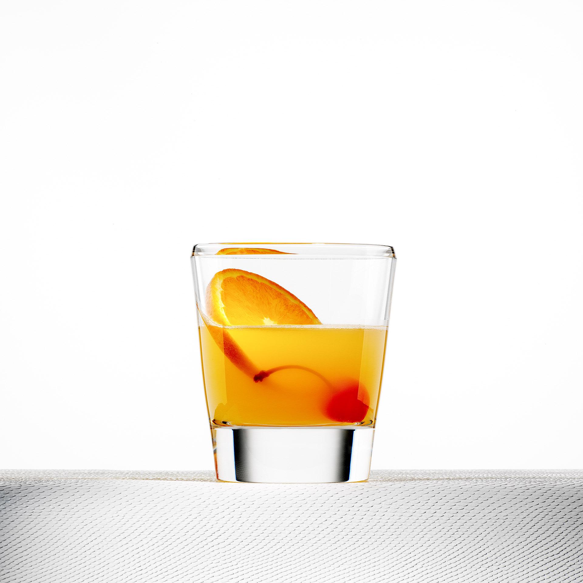 Whiskeyglas mit orangefarbenem Getränk und Obst. Feigefotodesign