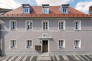 Graues Wohnhaus in Kemnath mit zehn weißen Fenstern an Weg mit Kopfsteinpflaster