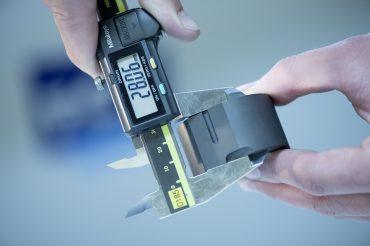 Nahaufnahme Hände Mitarbeiter mit Messgerät bei Kontrolle. Feigefotodesign