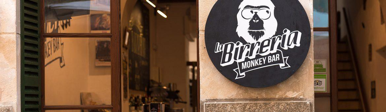 Schwarz weißes Logo an Steinfassade vor kleiner Bar in Tramuntana. Feigefotodesign
