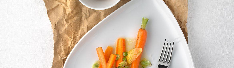 Marinierte Karotten auf Porzellanteller mit Brot in Schale auf Backpapier. Feigefotodesign