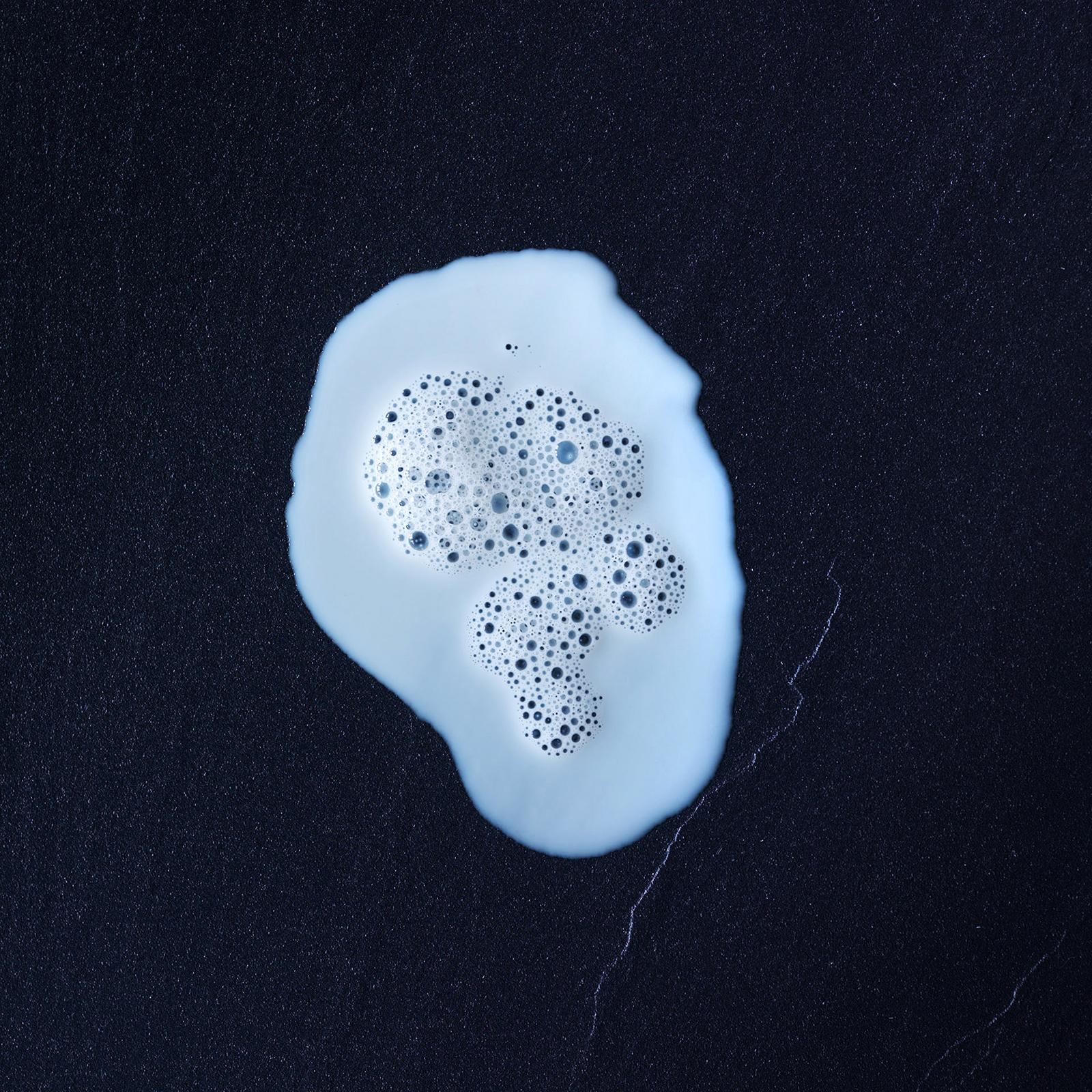 Schäumende Milch auf schwarzem Hintergrund. Feigefotodesign