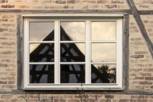 Spiegelung eines Fachwerkhauses in Fenster mit Holzrahmen