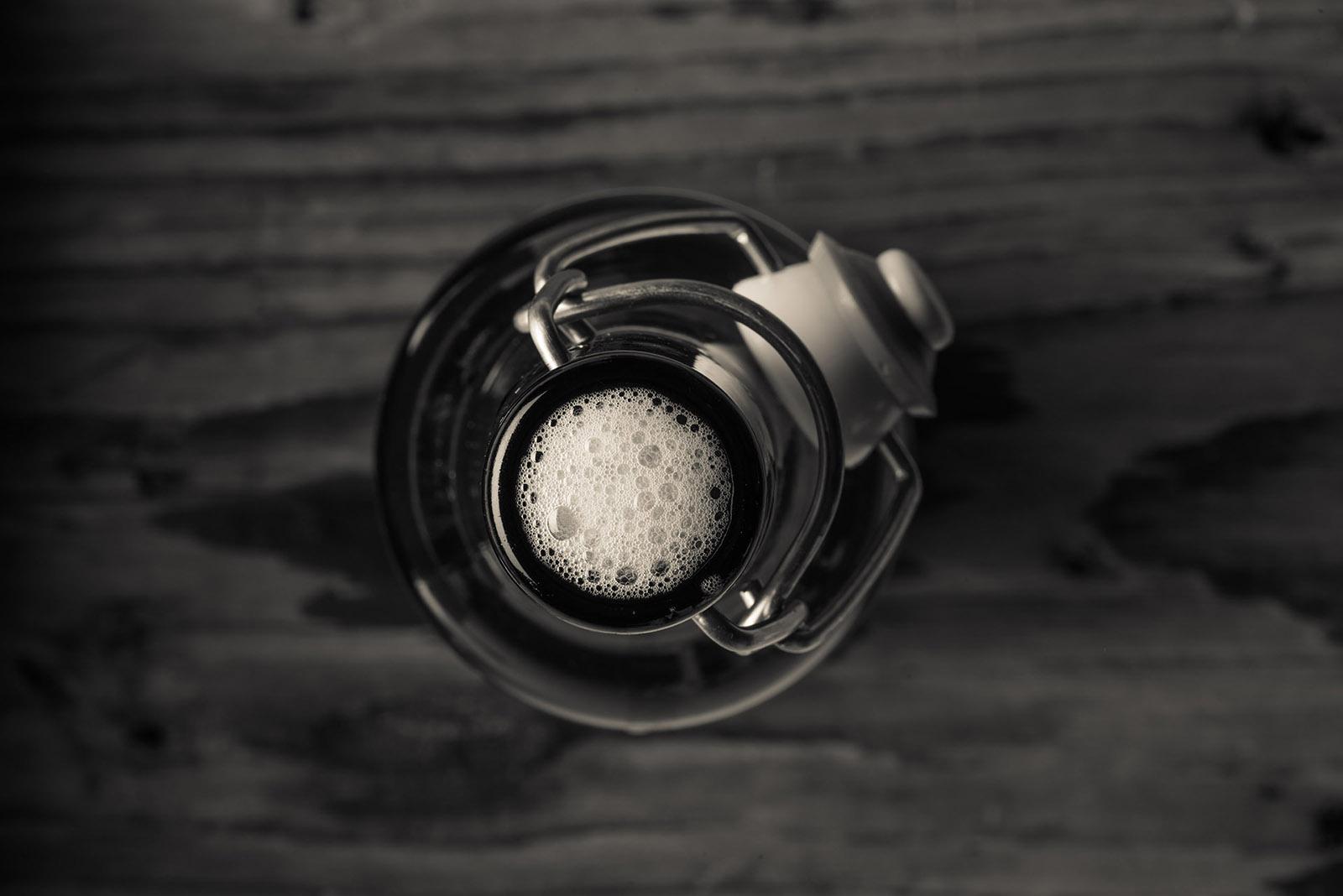 Geöffnete Bügelbierflasche mit Schaumkrone in Vogelperspektive und schwarz-weiß. Feigefotodesign