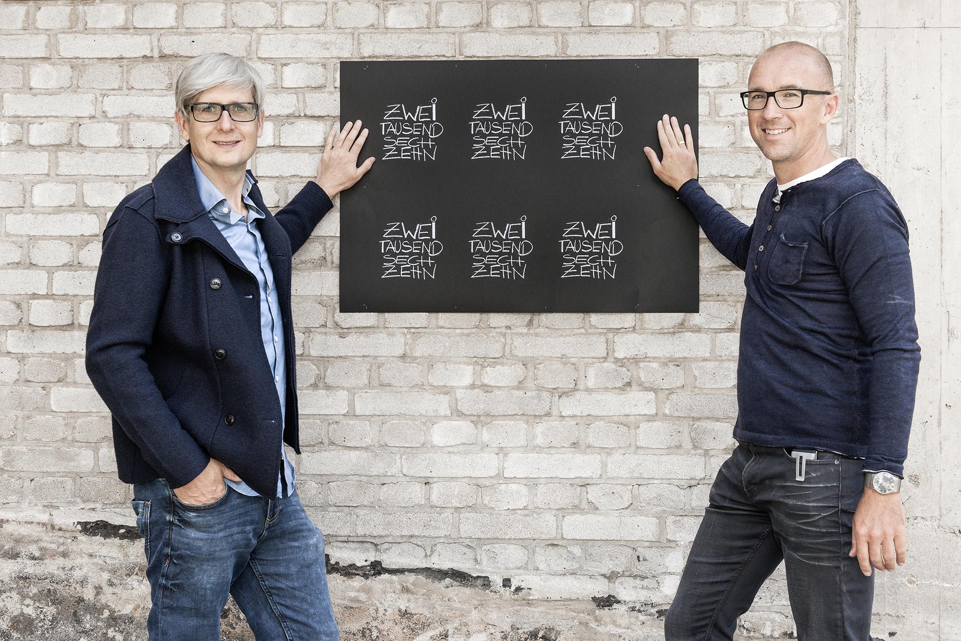 Fotograf Alexander Feig und Jürgen Frischmann stehen vor Backsteinwand Feigefotodesign