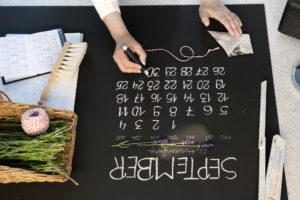 Handcrafted Fotokalender 2016 Hand schreibt Kalendertage mit weißer Kreide auf eine Tafel